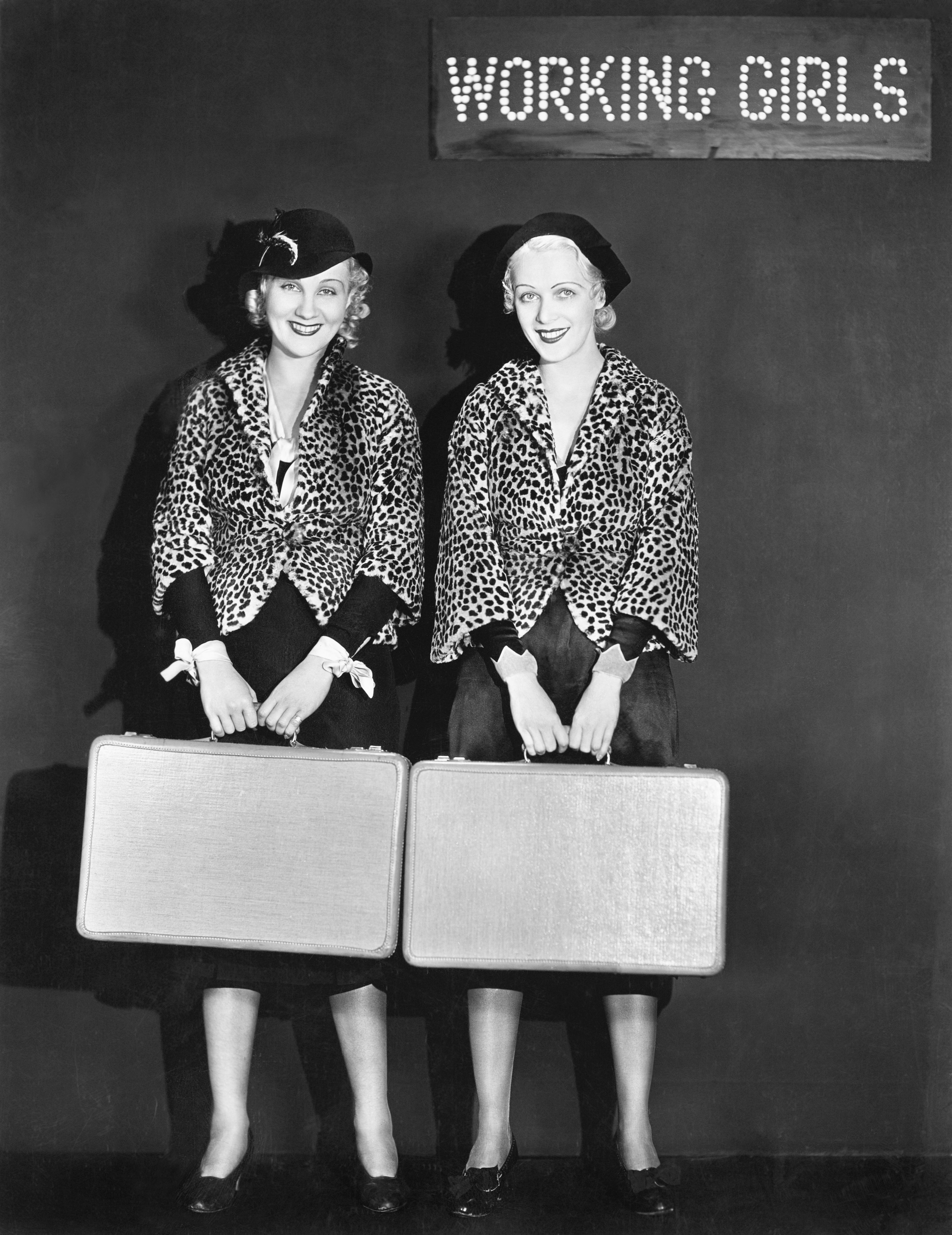 Portrait of two air hostess holding suitcases and smiling